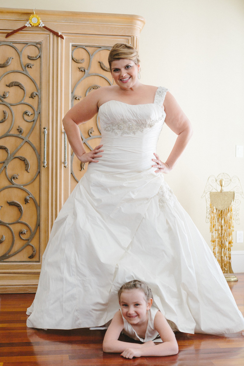 Fun Portrait of Bride with Flower Girl Peeking Out from Under Bridal Gown | The Majestic Vision Wedding Planning | Palm Beach Zoo in Palm Beach, FL | www.themajesticvision.com | Robert Madrid Photography