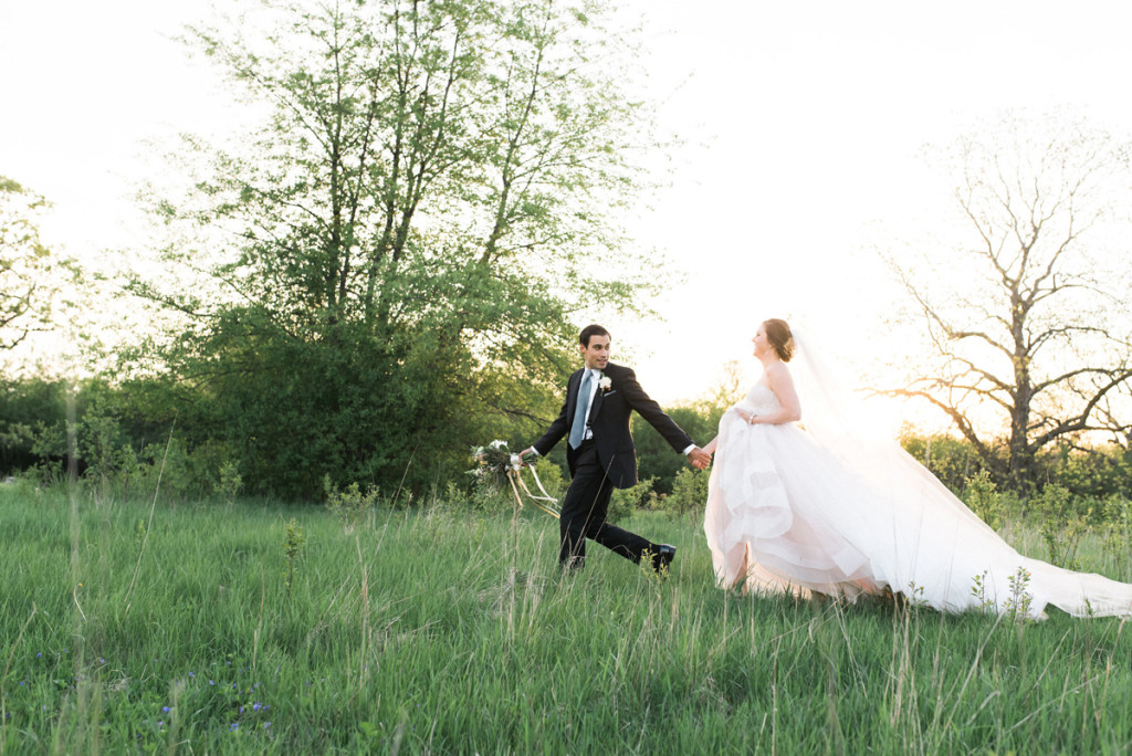 Beautiful Bride in Blush Tara Keely Gown Running Through a Field with Handsome Groom | The Majestic Vision Wedding Planning | Rustic Manor in Milwaukee, WI | www.themajesticvision.com | Elizabeth Haase Photography