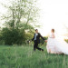 Beautiful Bride in Blush Tara Keely Gown Running Through a Field with Handsome Groom at Rustic Manor in Milwaukee, WI thumbnail