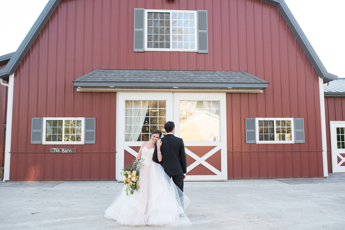 Beautiful Bride in Blush Tara Keely Gown With Handsome Groom in Front of Barn | The Majestic Vision Wedding Planning | Rustic Manor in Milwaukee, WI | www.themajesticvision.com | Elizabeth Haase Photography